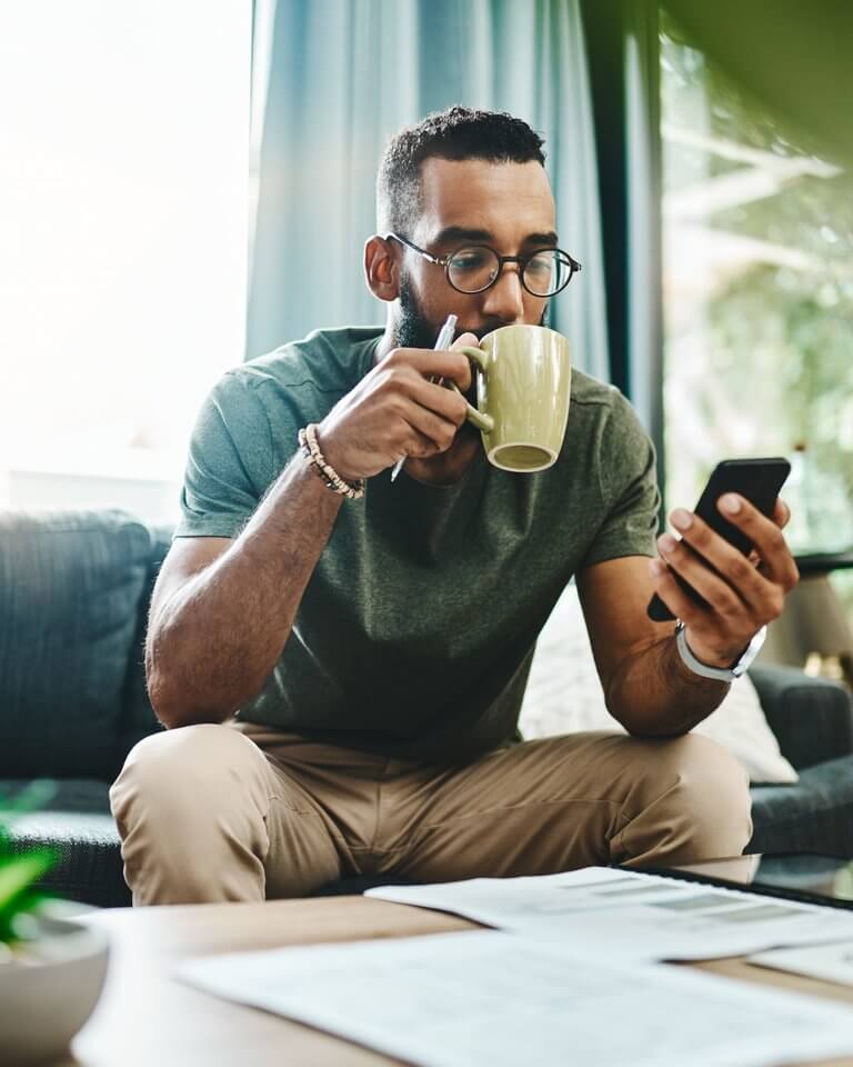tech - sitting man drinking coffee looking at phone