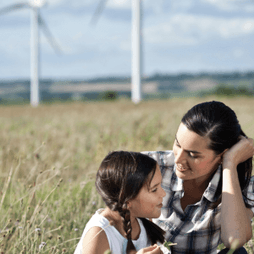 A woman and child together with a field and windmills visible in the distance.